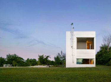 Moderní dům oblečený vzinku kouká z kukuřičného pole